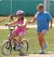 "Bicycle camp participant ""rides with the wind outside"" on a two-wheel bicycle"