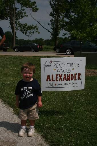 Alexander (AJ) Brewster, age 2, in front of his AJ's Angels sign