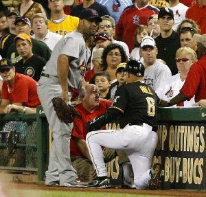 Pittsburgh Pirates first base coach Perry Hill (8) and Cardinals first baseman Albert Pujols (left) come to the aid of a fan who tried to retrieve a foul ball during the seventh inning of a game in Pittsburgh.