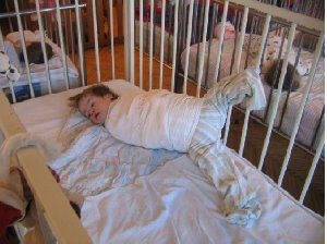 "MDRI investigators found this young child with Down's Syndrome, in Subotica Children's Institution, restrained to prevent ""self abuse"" - a product of mind-numbing boredom and lack of human contact. Photo MDRI 2006."